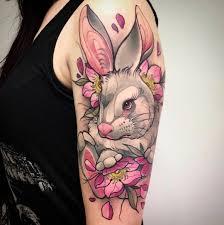 tatuaje grande de conejo con flores en el brazo